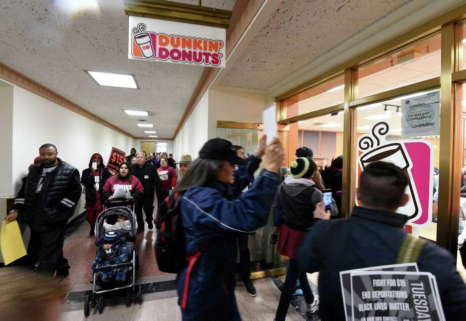 Minimum wage demonstrators march through the Dunkin Donuts store in the State Capitol Tuesday morning Nov. 10,  2015 in Albany, N.Y.  (Skip Dickstein/Times Union) Photo: SKIP DICKSTEIN / 00034174A