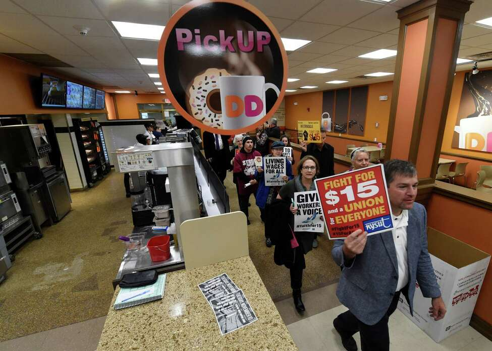 Minimum wage demonstrators march through the Dunkin Donuts store in the State Capitol Tuesday morning Nov. 10, 2015 in Albany, N.Y. (Skip Dickstein/Times Union)