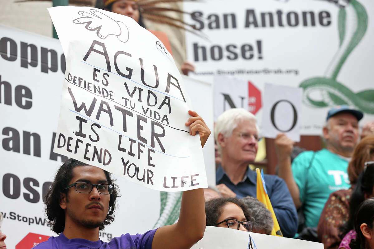 """Protestors display signs with slogans such as, """"Water is life,"""" in English and Spanish as they gather in front of City Hall to object to the San Antonio Water System's Vista Ridge pipeline project on Nov. 10, 2015."""
