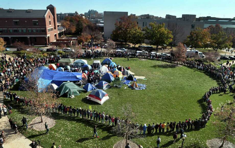 University of Missouri students circle tents on the Carnahan Quadrangle, locking arms to prevent media from entering the space following the resignation of President Tim Wolfe on Monday. Photo: Robert Cohen, MBR / St. Louis Post-Dispatch