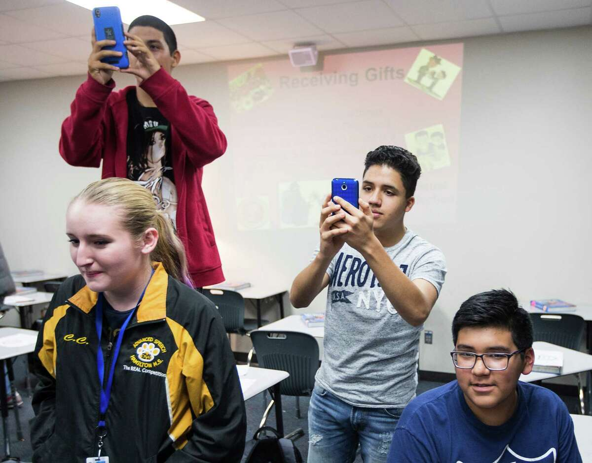 """Cypress Creek students take pictures as Houston Texans linebacker Brian Cushing awards teacher Erin Bryant as one of 10 """"Stars in the Classroom"""" on Tuesday, Nov. 10, 2015, in Houston."""