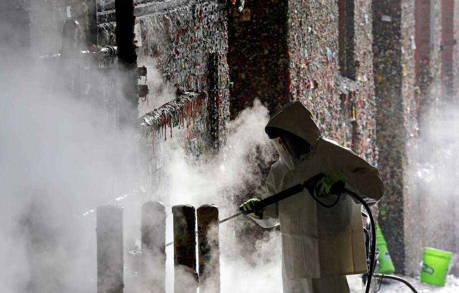 "A worker uses a steam cleaner Tuesday to remove decades of gum off Seattle's famed ""gum wall.""  that stretches behind and above him, Tuesday, Nov. 10, 2015, in Seattle. Tourists and locals have been sticking their used chewing gum to the wall near Pike Place Market for 20 years, leaving an estimated 1 million pieces in a kaleidoscope of colors, some stretched and pinched into messages, hearts and other designs. On Tuesday, cleaners began melting it all off. (AP Photo/Elaine Thompson) Photo: Elaine Thompson, STF / AP"