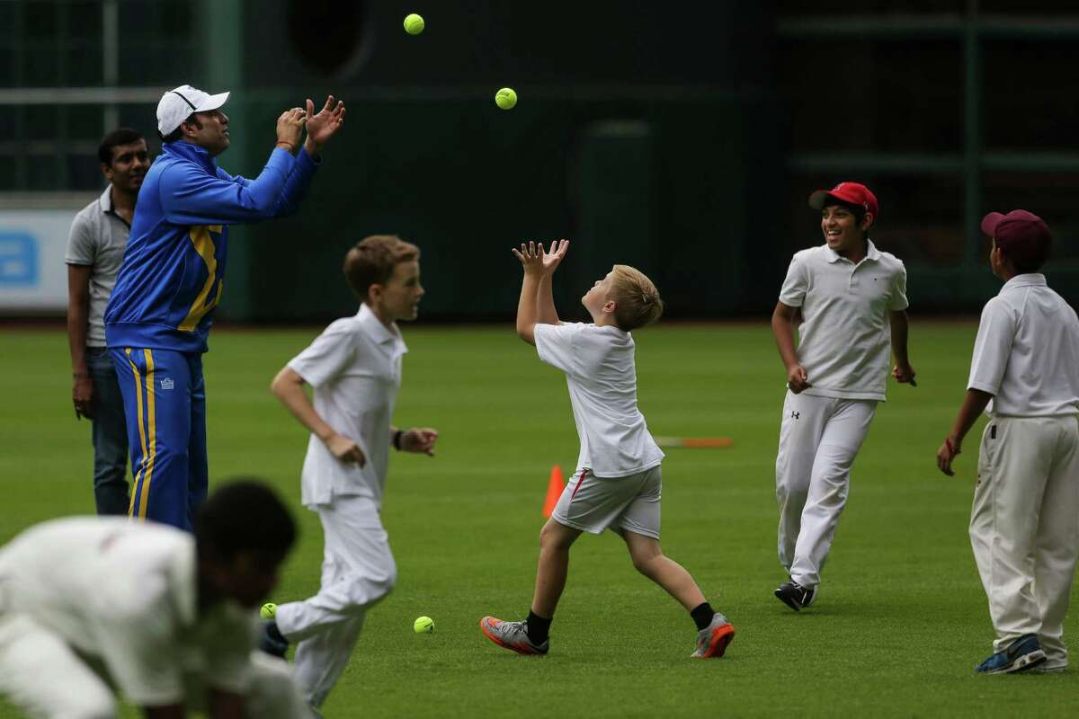 Former Indian cricketer VVS Laxman tosses balls with youths from the top area cricket academies during a clinic at Minute Maid Park on Tuesday.