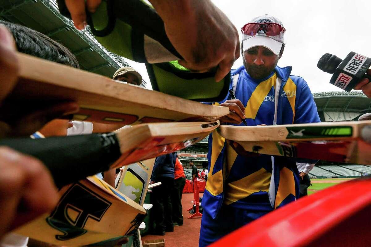 Former Sri Lankan cricketer Mahela Jayawardene signs bats for fans at Minute Maid Park on Tuesday.