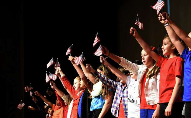 """Mike Quinn's 6th grade waves American flags during their singing of the Lee Greenwood song """"Proud to Be An American""""  during the Veteran's Day assembly at the Van Rensselaer Elementary School Tuesday morning Nov. 10,  2015 in Rensselaer, N.Y.  (Skip Dickstein/Times Union) Photo: SKIP DICKSTEIN / 00034013A"""