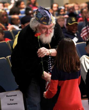 John Cleary, Son of the American Legion member receives a flower from a student during the Veteran's Day assembly at the Van Rensselaer Elementary School Tuesday morning Nov. 10,  2015 in Rensselaer, N.Y.  (Skip Dickstein/Times Union) Photo: SKIP DICKSTEIN / 00034013A