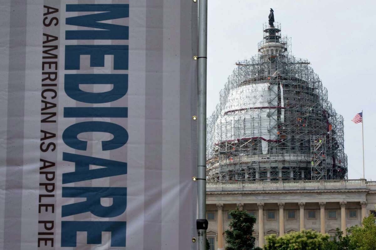 FILE - In this July 30, 2015 file photo, a sign supporting Medicare is seen on Capitol Hill in Washington. Most Medicare beneficiaries will keep paying the same monthly premium for outpatient care in 2016, the Obama administration said Tuesday, Nov. 10. (AP Photo/Jacquelyn Martin, File)