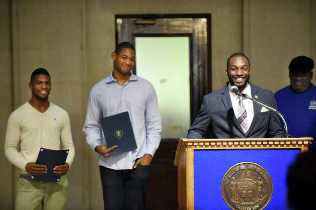 Commissioner of Recreation Jonathan Jones, second from right, recognizes the accomplishments of local boxers Abraham Nova, 21, left, and Brandon Lynch, 24, on Tuesday, Nov. 10, 2015, at City Hall in Albany, N.Y. The two men will compete in the Olympic Boxing Trials in Reno, Nev. in December. At far right is Jerrick Jones, director of the City of Albany Boxing Gym. (Cindy Schultz / Times Union) Photo: Cindy Schultz / 00034176A