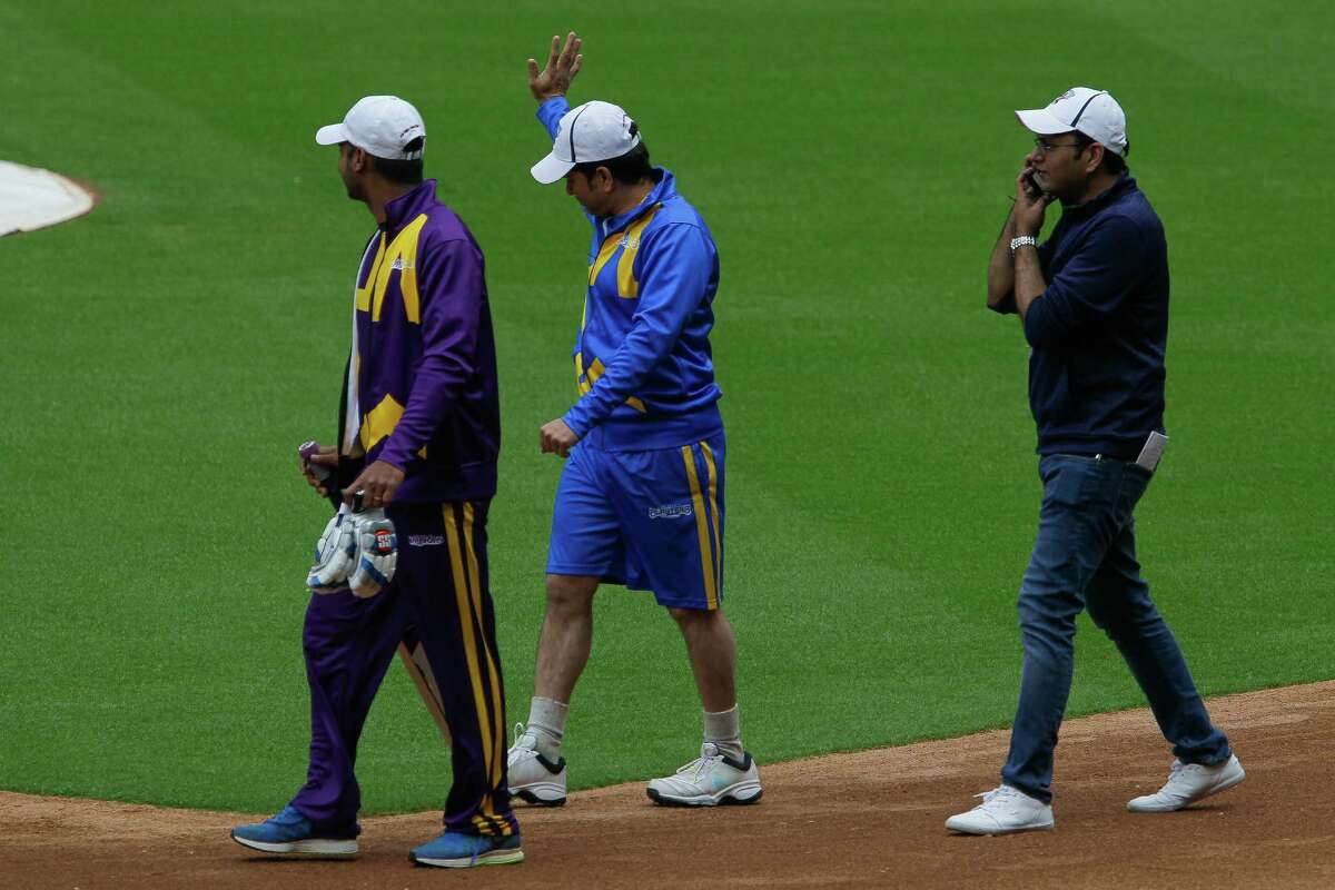 Former Indian cricketer Sachin Tendulkar, center, waives to a small crowd as he walks onto the field at Minute Maid Park Tuesday, Nov. 10, 2015, in Houston. On Wednesday, teams led by Tendulkar and Shane Warne will face off against each other in the the second Cricket All-Stars game.