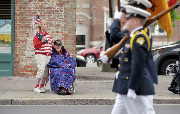 World War II Army Air Corps veteran Norman Jensen, 93, and his daughter Karen Covey watch as members of Christian Brothers Academy march by in the Albany Memorial Day Parade on Monday, May 25, 2015, in Albany, N.Y.  Jensen, who was a bombardier during the war, was the grand marshal of last years Veteran's Day Parade.  (Paul Buckowski / Times Union) Photo: PAUL BUCKOWSKI / 00031961A
