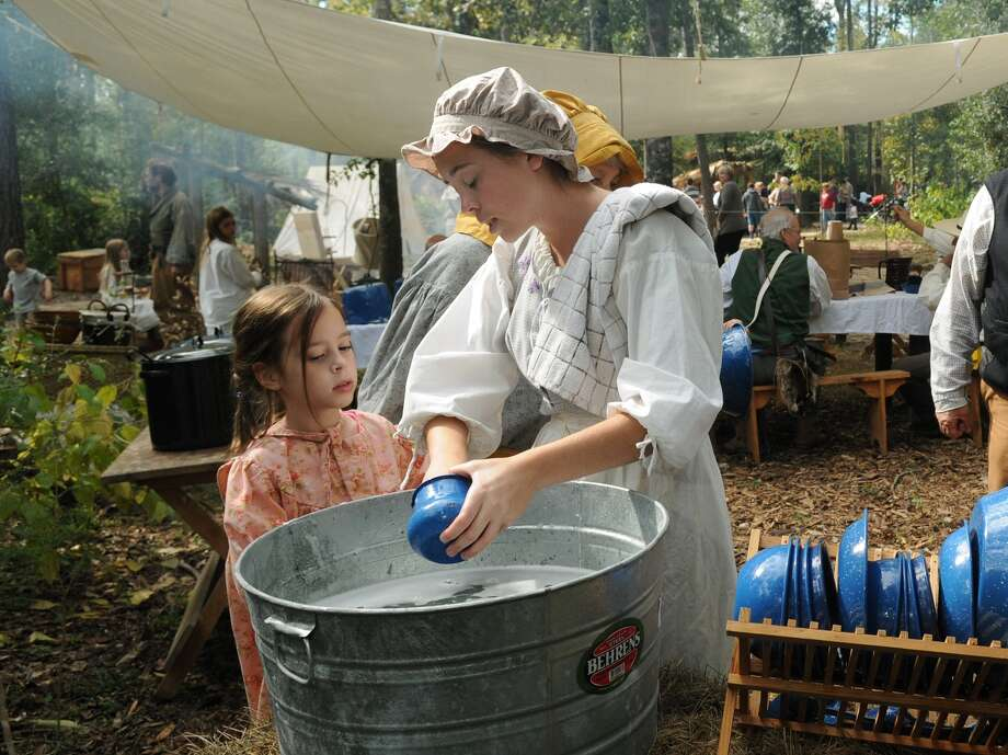 Dishwashing was an arduous task in 1830s Texas. A volunteer does kitchen duty at last year's  Pioneer Day at Jesse H. Jones Park and Nature Center. Photo: Jerry Baker, Freelance
