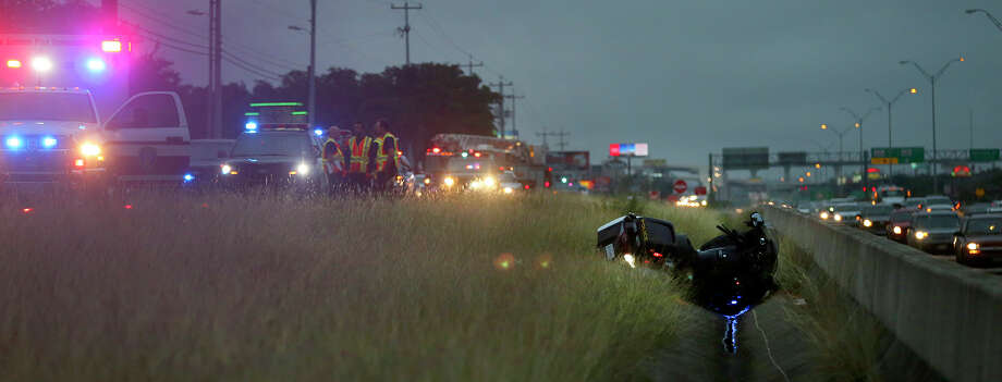 San Antonio police work Wednesday November 11, 2015 at the scene of an accident involving a San Antonio police motocycle officer and a female motorist driving a Toyota SUV on the southbound feeder road of U.S. highway 281 between Thousand Oaks and Brook Hollow. According to police sergeant Arthur Casas the woman driving the SUV pulled out of a parking lot shortly before 7:00 a.m. and collided with the officer who was on his way to work. The officer was forced into the grassy median and suffered injuries to his hand, ribs and face and was transported by EMS. The driver of the SUV, according to Casas, had abdominal injuries and will not be cited. Photo: John Davenport, San Antonio Express-News / ©San Antonio Express-News/John Davenport