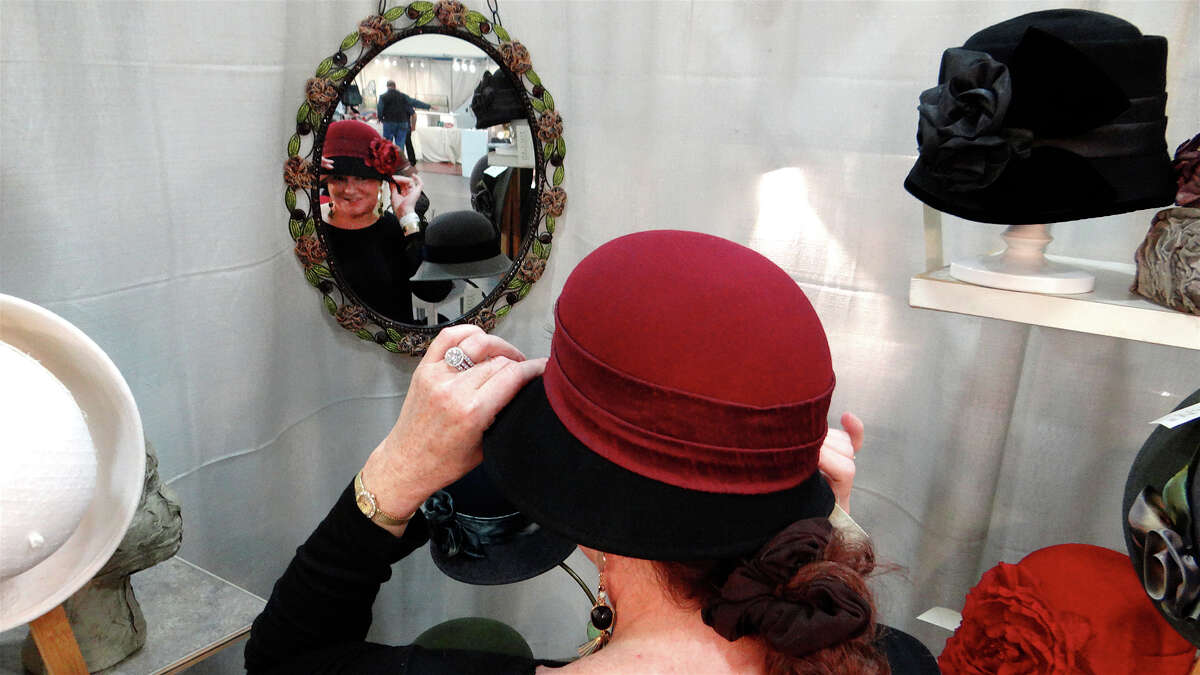 Susan Palmieri, of Fairfield, tries on a hat made by Toucan Hats on the opening day of the Westport Young Woman's League's annual Craft Westport artisan shopping experience on Saturday, Nov. 7, 2015.