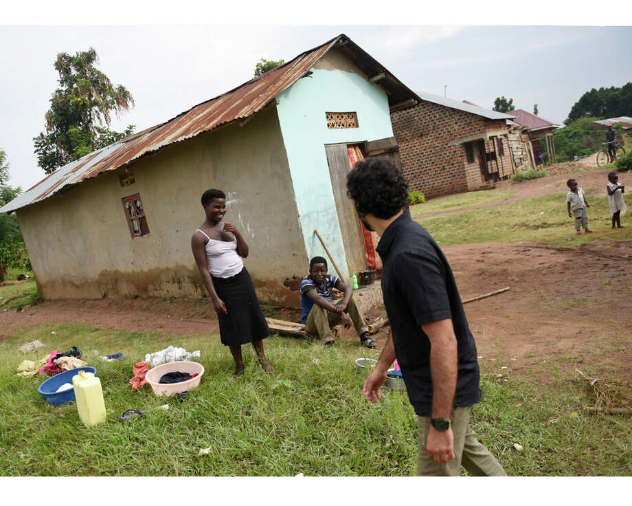 Dr. Sohi Ashraf, of Norwalk, Conn., walks through a small village on the way to an ACCESS Health Training Institute home visit in the rural town of Nakaseke, Uganda Wednesday, July 22, 2015. Photo: Tyler Sizemore / Hearst Connecticut Media / Greenwich Time