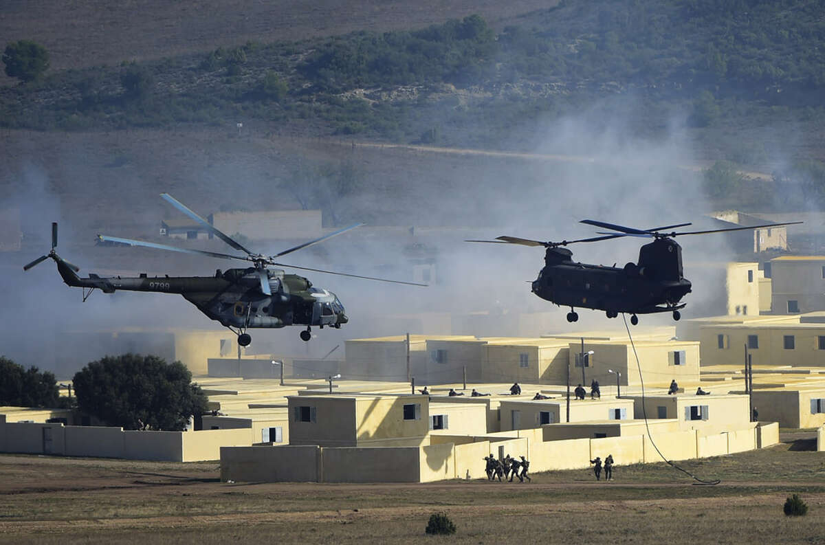 Two helicopters, a Mil Mi-17 (NATO reporting name Hip) (L) and a Chinook take part in the NATO's Trident Juncture Exercice at San Gregorio training ground near Zaragoza on November 4, 2015.