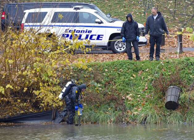 A police diver returned to the pond in Albany's Washington Park on Wednesday to resume the search for the knife investigators said they believe was used to kill Jacquelyn Porreca, a master barber, during an Aug. 21 at the Sand Creek Road salon where she worked. (Skip Dickstein / Times Union)