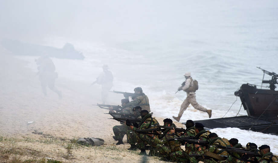 Portuguese Fuzileiros (front) secure the area after disembarking from an amphibious transport during an exercise as part of the NATO's Trident Juncture 2015 in Troia, 100 kms south of Lisbon on November 5, 2015. Photo: FRANCISCO LEONG, Getty Images, AFP, Leong / AFP