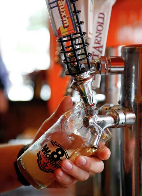 Bernie's Burger Bus restaurant Chef / Owner Justin Turner pours a local draft beer Wednesday, Sept. 17, 2014, in Houston.