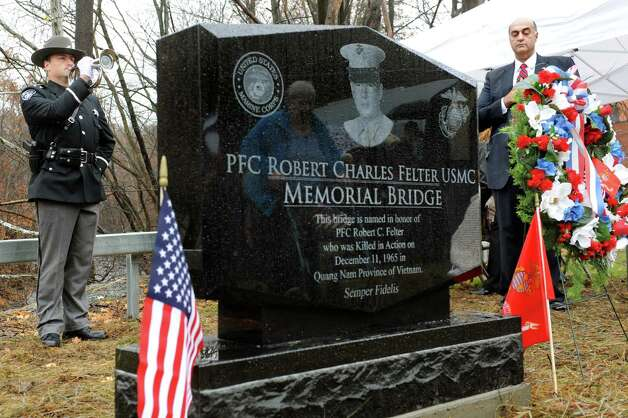 "Officer Gavin Boyer, left, plays ""Taps"" as Sheriff-Elect Pat Russo stands alongside the monument honoring Pfc. Robert C. Felter during the dedication of the Felter Memorial Bridge on Veterans Day on Wednesday, Nov. 11, 2015, in Troy, N.Y. Russo worked to convince the City Council to honor Felter, who grew up with Russo on Spring Avenue near the bridge and was killed in action during the Vietnam War. (Cindy Schultz / Times Union) Photo: Cindy Schultz / 00034128A"