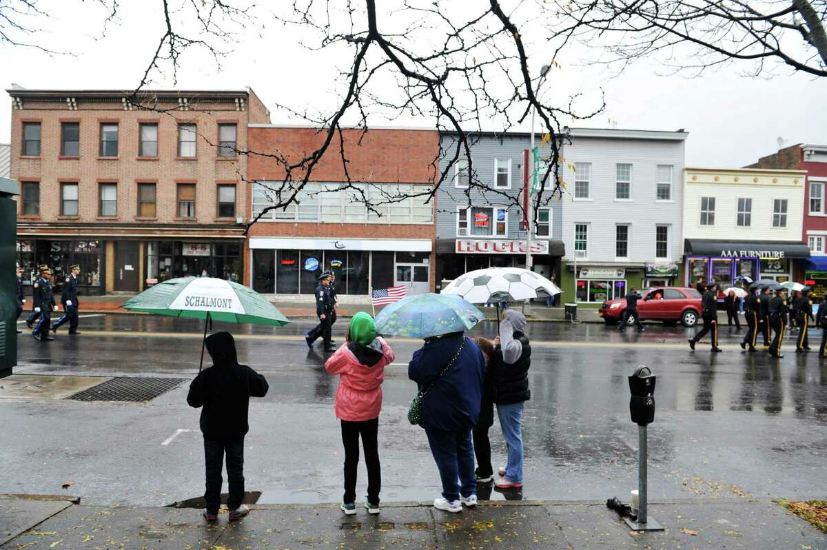 People use umbrellas to shield themselves from the rain as they watch the 64th Annual Albany Veterans Day Parade on Wednesday, Nov. 11, 2015, in Albany, N.Y.(Paul Buckowski / Times Union)