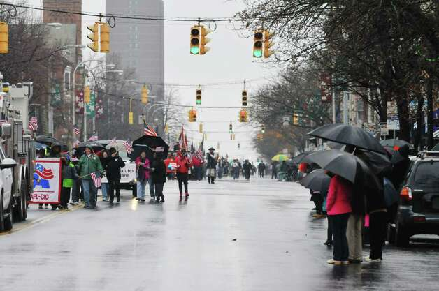 People use umbrellas to shield themselves from the rain as they watch the 64th Annual Albany Veterans Day Parade on Wednesday, Nov. 11, 2015, in Albany, N.Y.(Paul Buckowski / Times Union) Photo: PAUL BUCKOWSKI / 00034155A