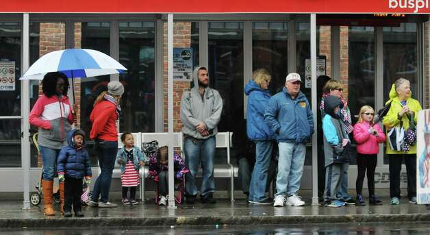 People stand inside a bus shelter on Central Ave. to shield themselves from the rain as they watch the 64th Annual Albany Veterans Day Parade on Wednesday, Nov. 11, 2015, in Albany, N.Y.(Paul Buckowski / Times Union) Photo: PAUL BUCKOWSKI / 00034155A