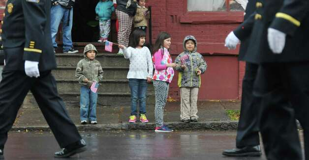 Carlos Santacruz, left, 6, and his sisters Melinda Santacruz, 8, and Lunesta Santacruz, 8, along with their cousin, Emilio Santacruz, 6, watch the 64th Annual Albany Veterans Day Parade from outside their apartment on Wednesday, Nov. 11, 2015, in Albany, N.Y.  (Paul Buckowski / Times Union) Photo: PAUL BUCKOWSKI / 00034155A