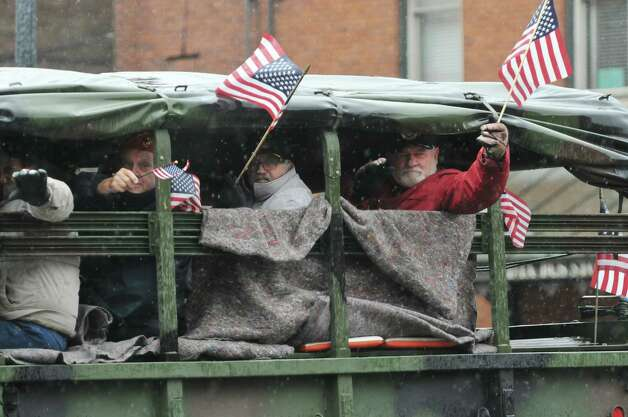 Veterans wave flags  ride in the back of a military truck for the Veterans Miracle Center, as they take part in 64th Annual Albany Veterans Day Parade from outside their apartment on Wednesday, Nov. 11, 2015, in Albany, N.Y.  (Paul Buckowski / Times Union) Photo: PAUL BUCKOWSKI / 00034155A