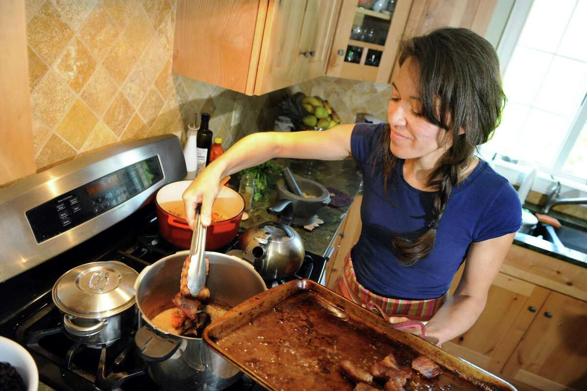 Ellie Markovitch, a native of Brazil, cooks a national dish at her home on Wednesday, May 21, 2014, in Brunswick, N.Y. (Cindy Schultz / Times Union) ORG XMIT: MER2014052214182885