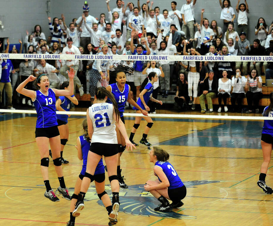 Ludlowe players celebrate a point against Darien in the 2015 FCIAC Championships last Saturday at Ludlowe. The Falcons defeated the Blue Wave in four sets to win the FCIAC title. It was the first time ever that Darien had lost in a conference final meet. Photo: Christian Abraham / Hearst Connecticut Media / Connecticut Post