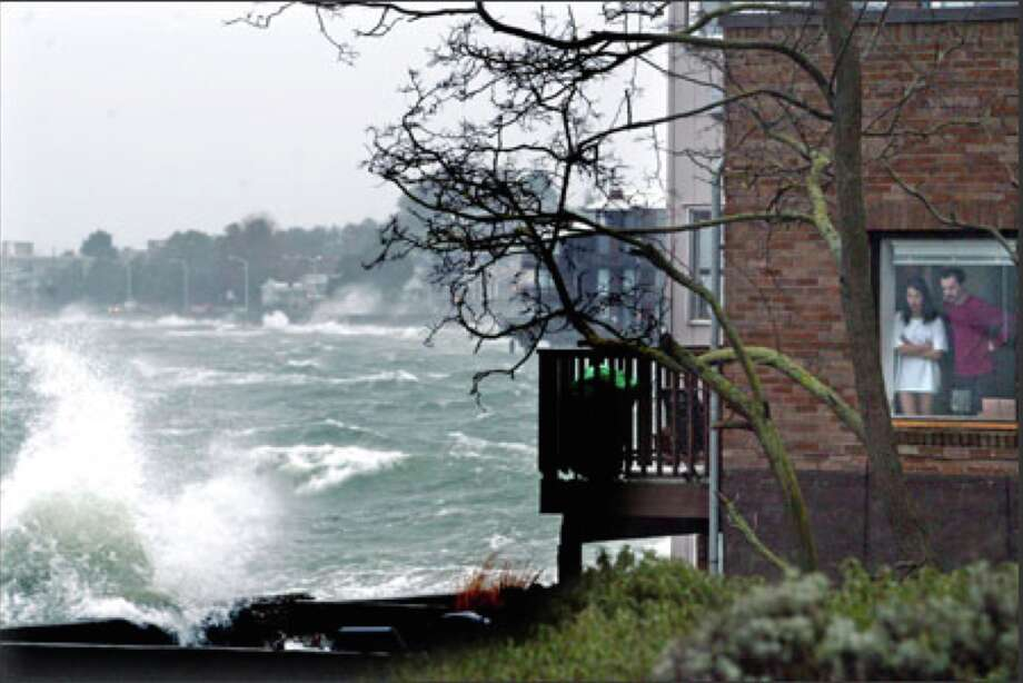 A couple watch as a combination of high tides and strong wind causes waves to crash over the bulkhead of their building on Beach Drive in Alki in 2006.