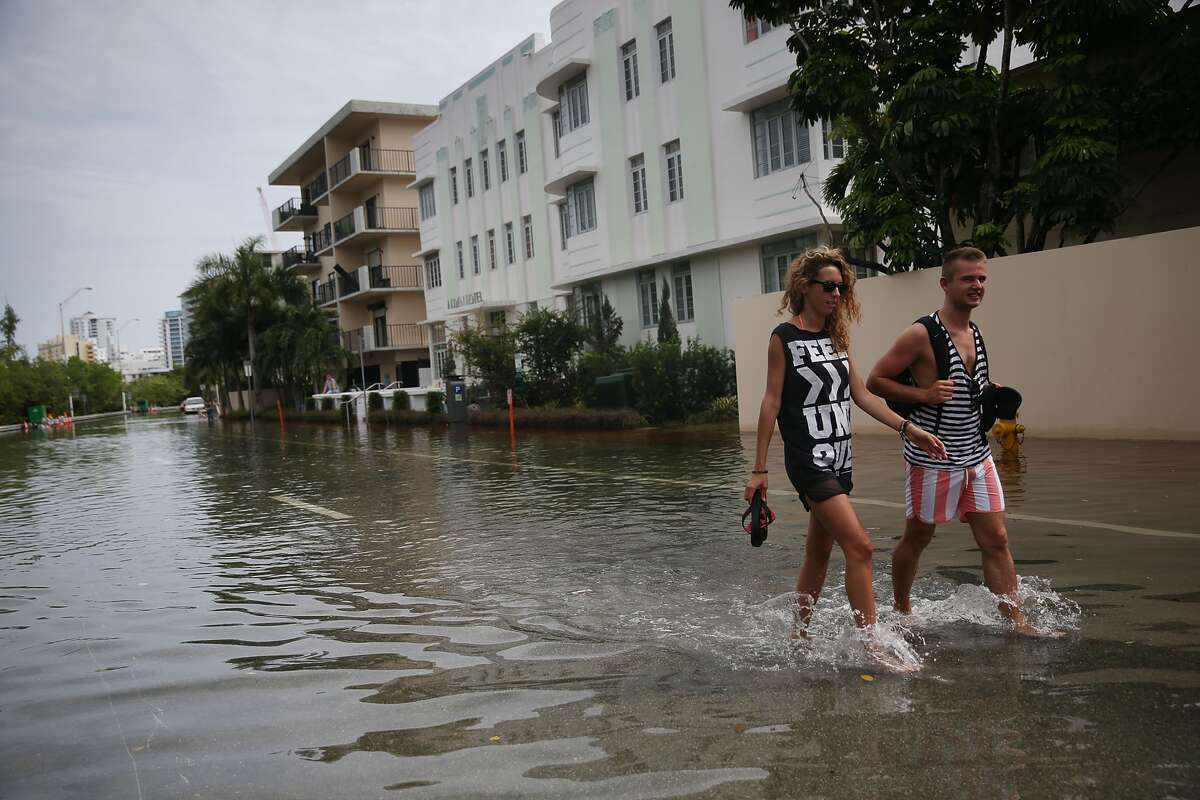 People walk through a flooded street that was caused by the combination of the lunar orbit which caused seasonal high tides and what many believe is the rising sea levels due to climate change on September 29, 2015 in Miami Beach, Florida. The City of Miami Beach is in the middle of a five-year, $400 million storm water pump program and other projects that city officials hope will keep the ocean waters from inundating the city as the oceans rise even more in the future.