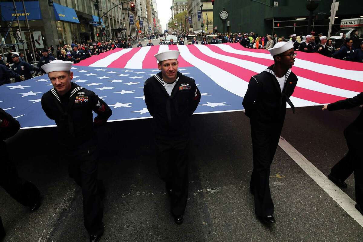 """NEW YORK, NY - NOVEMBER 11: Members of the U.S. Navy march with the American Flag in the the nation's largest Veterans Day Parade in New York City on November 11, 2015 in New York City. Known as """"America's Parade"""" it features over 20,000 participants, including veterans of numerous eras, military units, businesses and high school bands and civic and youth groups."""