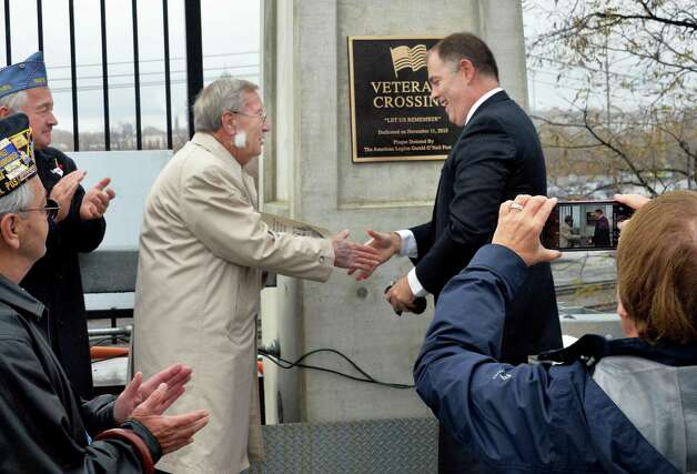 Planning director Charles Moore, left, and Mayor Daniel Dwyer unveil the plaque renaming the Broadway Viaduct Bridge as Veteran Crossing during a Veteran's Day ceremony Wednesday, Nov. 11, 2015, in Rensselaer, N.Y.  (John Carl D'Annibale / Times Union) Photo: John Carl D'Annibale / 00034125A
