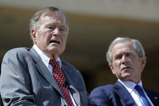 In this 2013 file photo, former Presidents George H.W. Bush and George W. Bush attend the George W. Bush Presidential Center dedication ceremony in Dallas. The father has offered a tough critique of his son's presidency in a new biography.