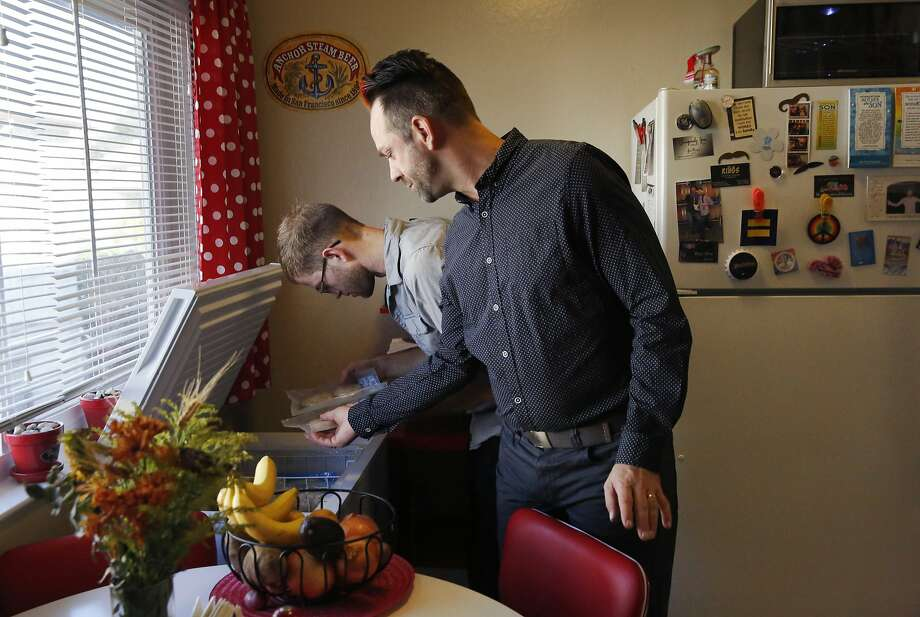 From left, Andrew and Jeramie Andehueson get frozen food out of a freezer for lunch in their apartment Nov. 11, 2015 in Alameda, Calif. The Andehueson's moved to the Bay Area from South Dakota to pursue their careers and eventually a family. Last week, after only a year at their apartment, they received an eviction notice with no explanation on their door. Photo: Leah Millis, The Chronicle