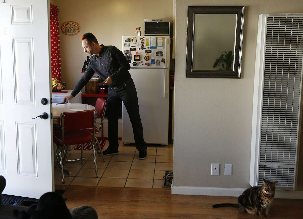 Jeramie Andehueson sets the table for lunch with his husband Andrew in their apartment as their cats Nala, right and Mufasa, lower left, hang out in the living room Nov. 11, 2015 in Alameda, Calif. The Andehueson's moved to the Bay Area from South Dakota to pursue their careers and eventually a family. Last week, after only a year at their apartment, they received an eviction notice with no explanation on their door.