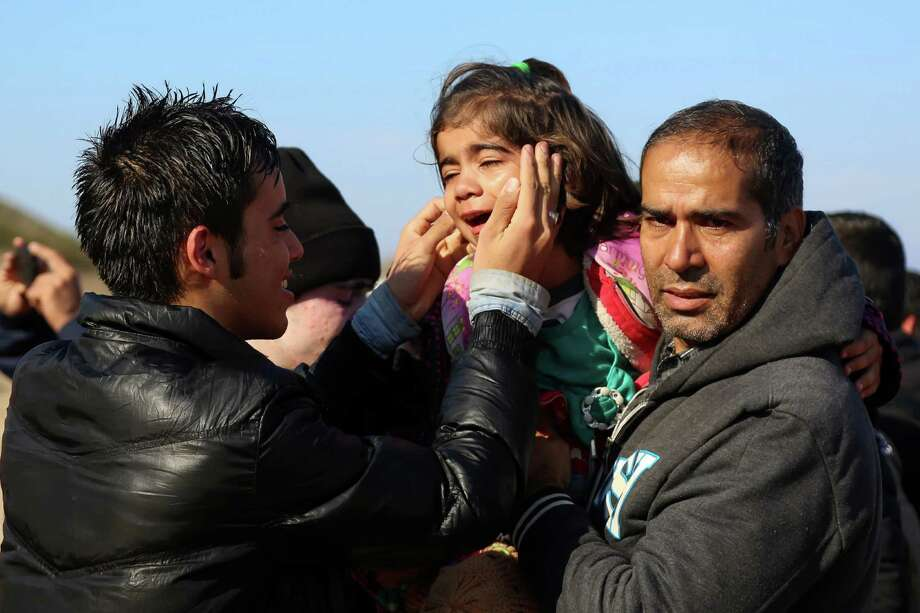 A man tries to calm a girl who arrived with her family on a dinghy from the Turkish coast to the Skala Sikaminias village on the northeastern Greek island of Lesbos on Wednesday, Nov. 11, 2015. More than 770,000 people have arrived in the EU by sea so far this year overwhelming border authorities and receptions centers. (Manolis Lagoutaris/InTime News via AP)  GREECE OUT Photo: Manolis Lagoutaris, STR / InTime News