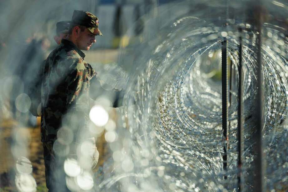 Slovenian soldiers build a razor wire fence Wednesday on the Slovenian-Croatian border in Gibina. The country's prime minister says if Austria restricts its borders, Slovenia won't be able to handle the influx of migrants. Photo: JURE MAKOVEC, Stringer / Jure Makovec/AFP
