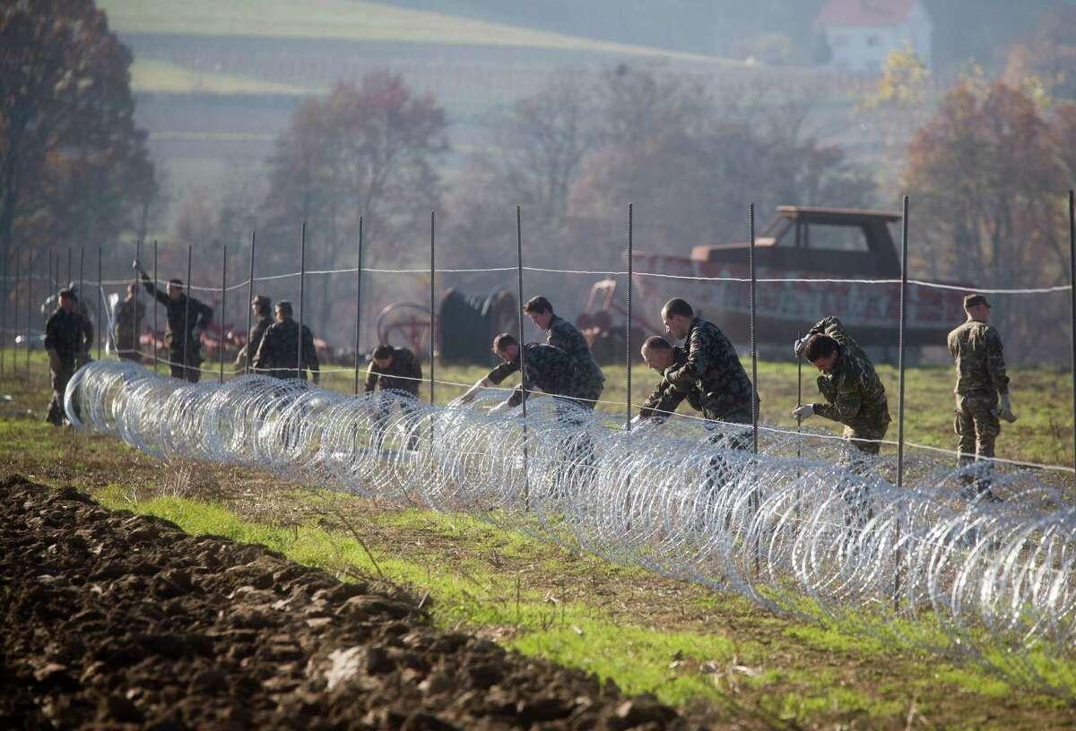 Slovenia-Croatia Slovenian soldiers erect a razor-wired fence on the Croatian border in Gibina, Slovenia, Wednesday, Nov. 11, 2015. Slovenia has started erecting a barbed-wire fence on the border with Croatia to prevent uncontrolled entry of migrants into the already overwhelmed alpine state. (AP Photo/Darko Bandic)