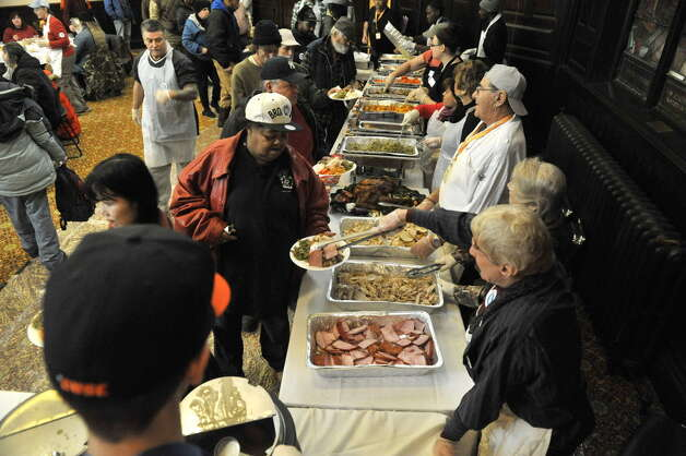 Volunteers dish out food at the annual Equinox Thanksgiving Day Community Dinner at the First Presbyterian Church in Albany. (Paul Buckowski / Times Union)