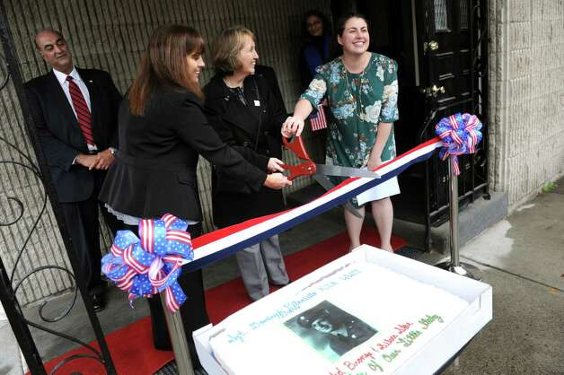 Domenica Pasinella, right, joins Rensselaer County Executive Kathy Jimino, center, and Donna Cioffi in cutting the ribbon to open a housing facility for veterans on Wednesday, Nov. 11, 2015, at the Dominick Pitaniello Veteran and Community Housing in Troy, N.Y. The facility is named for Pasinella's great uncle, who was killed in action as a young man during WWII. At left is Rensselaer County Sheriff-Elect Pat Russo. (Cindy Schultz / Times Union) Photo: Cindy Schultz / 00034105A