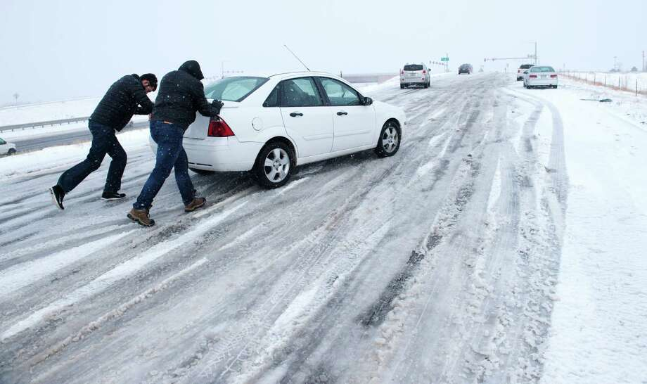 Curtis Hansen, left, and Jeff Malley push a motorist up the icy northbound off-ramp from I-25 to Baptist Road, north of Colorado Springs, Colo. on Wednesday. The storm system that dropped a foot of snow in the Rockies was making travel hazardous as it headed east on Wednesday.  Photo: Mark Reis, MBI / The Gazette