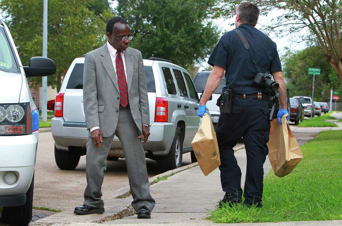 Innocent Onyeri, whose son Chimene Onyeri is being held by police for questioning in the attack on state District Judge Julie Kocurek, watches evidence be removed from his home in Alief, Tuesday, Nov. 10, 2015. ( Mark Mulligan / Houston Chronicle )