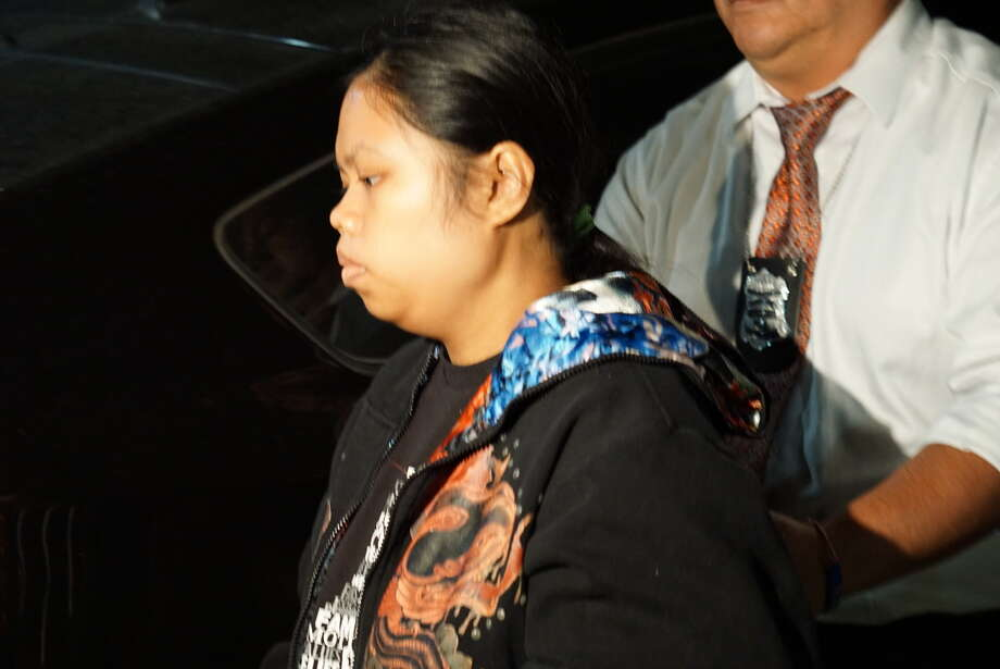 Roseanne Welch, 25, accused of abandoning a child in a toilet Halloween night at a Northeast Side VIA Park and Ride, is escorted by San Antonio Police to an SUV Wednesday night, Nov. 11, in the 4th floor parking garage of the San Antonio Public Safety Headquarters, 315 South Santa Rosa St. Photo: Jacob Beltran / Jacob Beltran