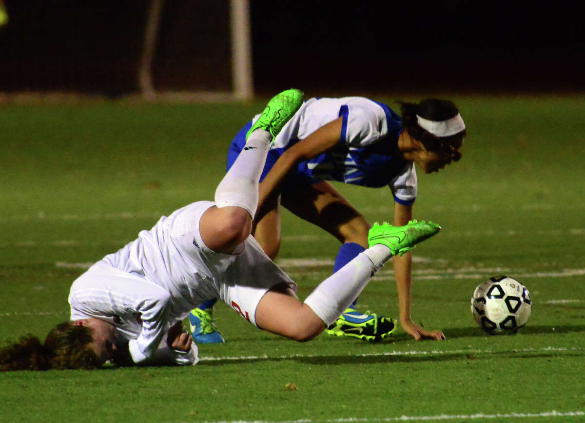 Fairfield Warde's Anna Glovin spills onto the ground after colliding with Hall's Gianna Dionicio during second round of CIAC Girls Soccer Tournament action in Fairfield, Conn., on Wednesday Nov. 11, 2015.