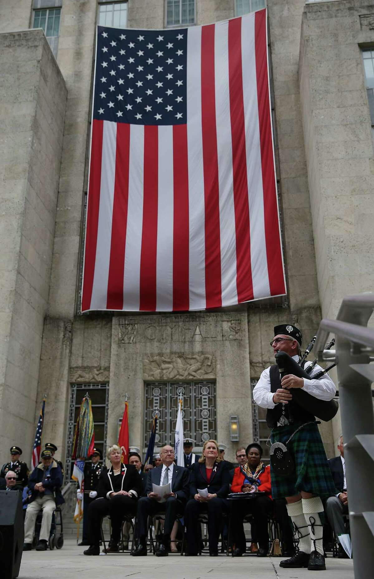"""Bagpiper Ian Martin performs an """"American Set"""" melody of songs on the steps of Houston City Hall during the Veteran's Day ceremonies on Wednesday, Nov. 11, 2015, in Houston."""