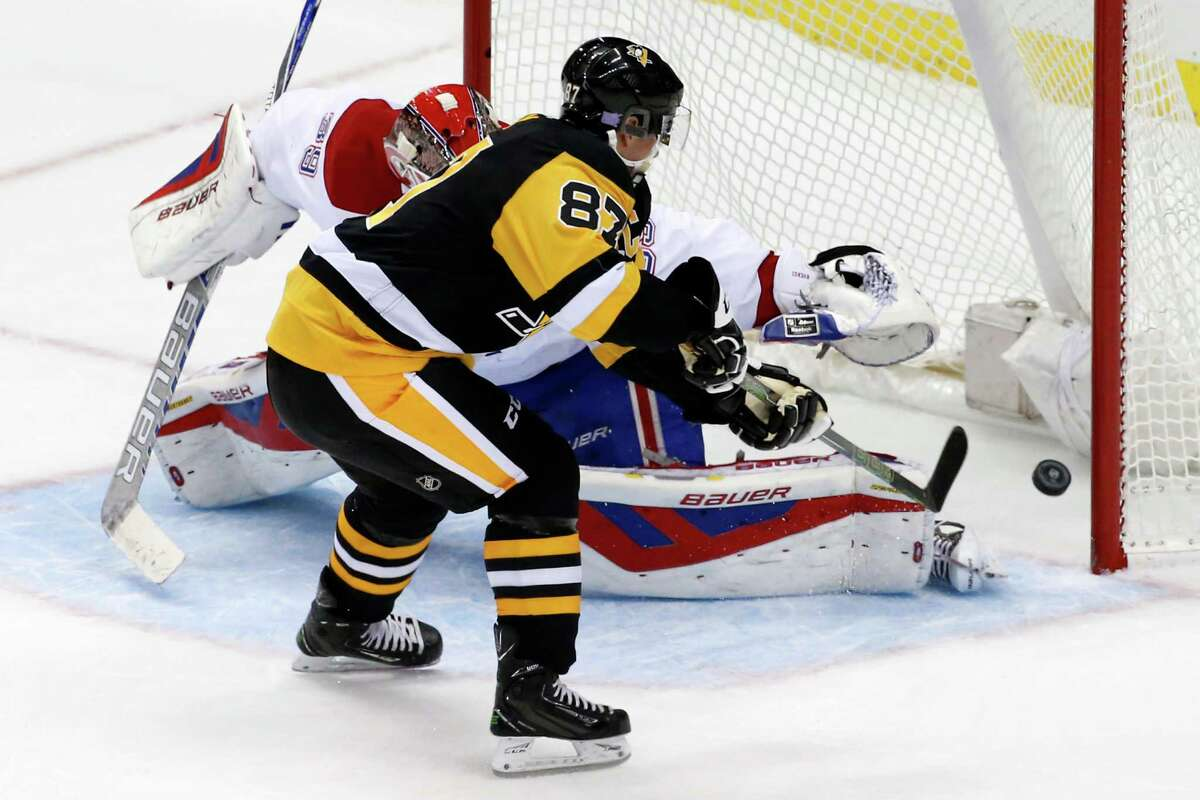 Pittsburgh Penguins' Sidney Crosby (87) backhands the game-winning shootout goal behind Montreal Canadiens goalie Mike Condon (39) during an NHL hockey game in Pittsburgh, Wednesday, Nov. 11, 2015. The Penguins won in a shootout 4-3. (AP Photo/Gene J. Puskar) ORG XMIT: PAGP110