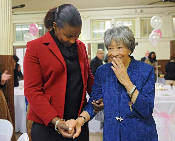 Sylvia Hill, known as Mother Hill, right, holds the hand of her great niece Naomi Clarke of Albany as members of Wilborn Temple Church of God in Christ celebrate her 100th birthday at Wilborn Temple on Wednesday, Nov. 11, 2015 in Albany, N.Y.  (Lori Van Buren / Times Union) Photo: Lori Van Buren / 00034206A
