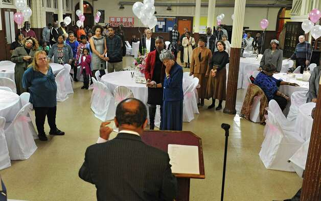 Pastor Solomon Dees, foreground, says a prayer for Sylvia Hill, known as Mother Hill, center, while she holds the hand of her great niece Naomi Clarke of Albany as members of Wilborn Temple Church of God in Christ celebrate her 100th birthday at Wilborn Temple on Wednesday, Nov. 11, 2015 in Albany, N.Y.  (Lori Van Buren / Times Union) Photo: Lori Van Buren / 00034206A
